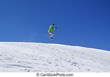 Snowboarder jump in snow park at ski resort on sun day