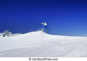 Snowboarder jump in snow park at ski resort on sunny winter day