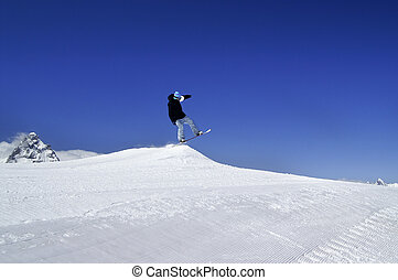 Snowboarder jump in terrain park at ski resort on sun winter day