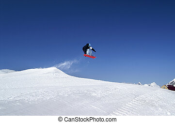 Snowboarder jump in terrain park at ski resort on sunny winter day