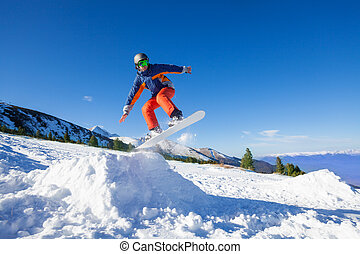 Snowboarder jumping high from hill in winter with beautiful...