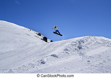 Snowboarder jumping in snow park at ski resort on sunny winter day