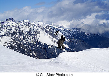Snowboarder jumping in snow park at ski resort on winter day