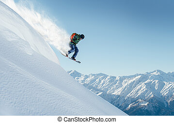 snowboarder jumping on steep mountainside - snowboarder...