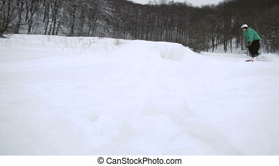 Snowboarder Jumping Snow Slope - Snowboarder man in green...