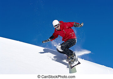 Snowboarder jumping through air with deep blue sky in...