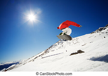 Snowboarder jumping with blue sky in background
