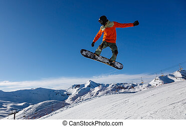 Snowboarder jumps in snow park in the snowy mountains in Livigno, Italy