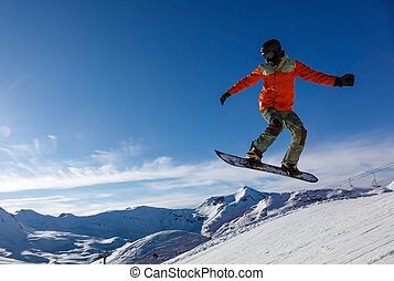 Snowboarder jumps in snow park in the snowy mountains