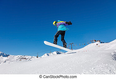 Snowboarder jumps in the snowy mountains