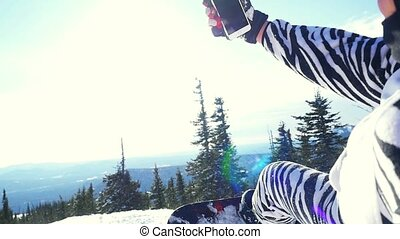 Snowboarder man in suit of kigurumi of zebra take selfie with phone over mountains