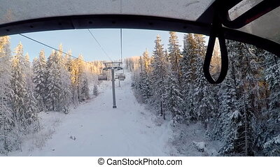 Snowboarder moving up the mountain with the chairlift