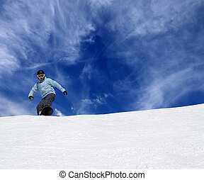Snowboarder on off piste slope and blue sky with clouds