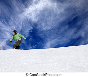 Snowboarder on off-piste slope and blue sky with clouds