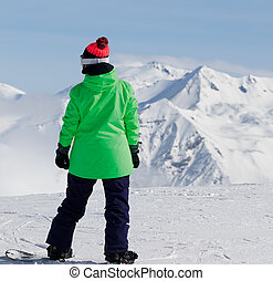 Snowboarder on top of mountain before downhill