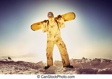 Snowboarder posing on blue sky backdrop in mountains