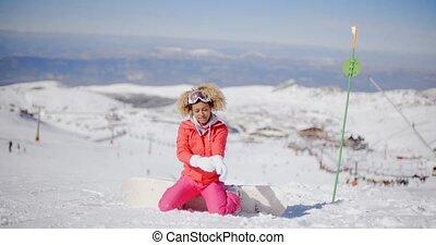 Snowboarder putting on her gloves - Cute female snowboarder...