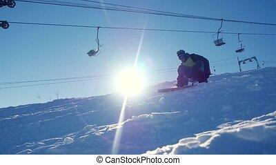 Snowboarder rides through the sun in mountains on ski resort...