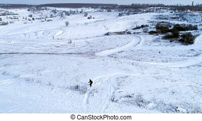 Snowboarder riding down the slope, aerial view - Snowboarder...