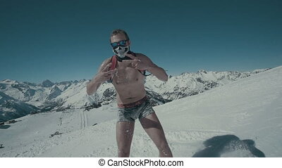 snowboarder riding in shorts in high mountains