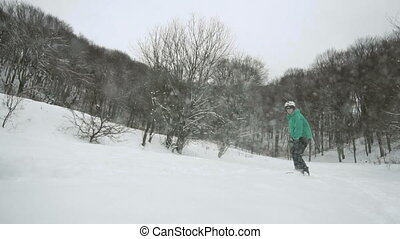 Snowboarder Slides Snow Slope - Young man snowboarder in...