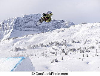 Snowboarder spinning doing a grab in the air