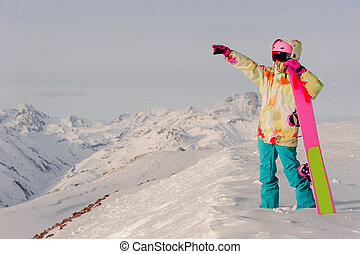 Snowboarder standing with snowboard in one hand and enjoying...