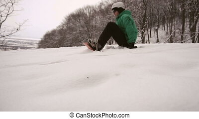 Snowboarder Starts Slide Slope - Snowboarder man in green...
