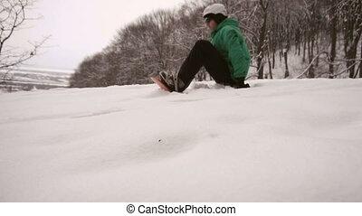 Snowboarder Starts Slide Slope - Snowboarder man in green...