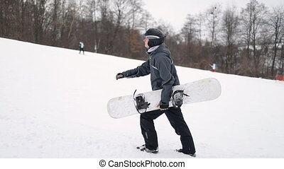 Snowboarder Walking up the Mountain for Skiing