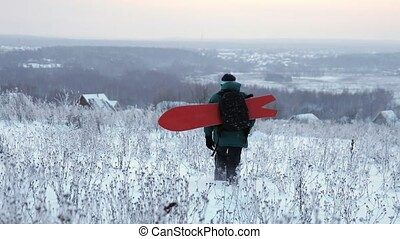 Snowboarder walks with snowboard at wild field Switzerland....
