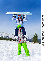 Snowboarder with girl sitting on his shoulders