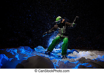 Snowboarder woman dressed in a green sportswear riding on the mountain slope