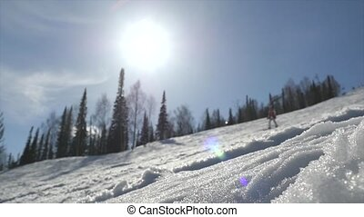 Snowboarder woman on a slope in slow motion through the sun...
