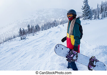 Snowboarder woman on a snowy slope in the mountains.