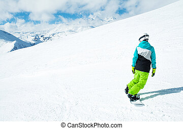 Snowboarder woman on background landscape of snowy high mountains