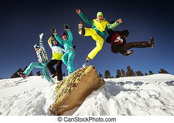 Snowboarders jump on blue sky backdrop in mountains