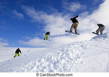 Four snowboarders mid air of a big jump on a beautiful day to be out on the mountain.