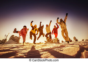 Snowboarders posing on blue sky backdrop in mountains -...