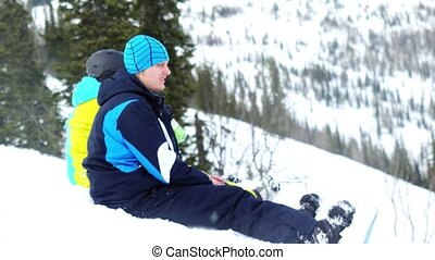 Snowboarders sitting in the mountains on ski resort.