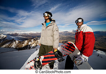 Snowboarders - Two snowboarders stand on a peak over looking...