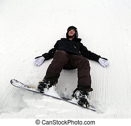 A beginning snowboarder falls down laughing in the snow.