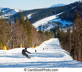 Snowborder on a piste - Snowborder going down the slope at ...