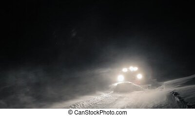 Snowcat preparing a slope at night in high mountains at...