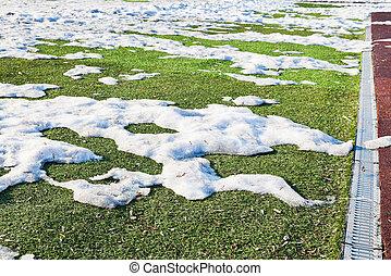 snowdrifts on outdoor soccer field in spring low season