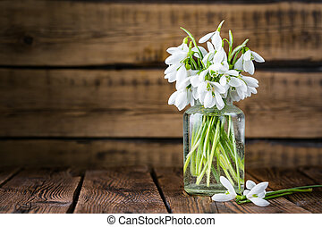 snowdrops in a glass vase on a wooden background, spring bouquet