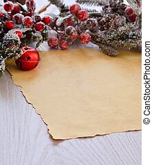 Snowed fur-tree branch with berries above wrapping paper