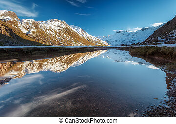 Snowed mountain reflection in the river