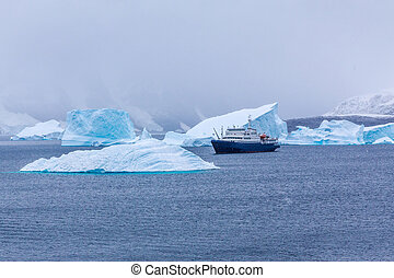Snowfall and cruise liner among blue icebergs in Port Charcot, Booth Island, Antarctic