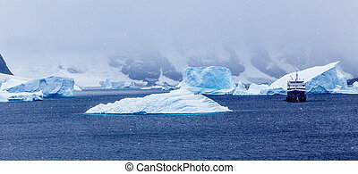 Snowfall and cruise ship among blue icebergs in Port Charcot, Booth Island, Antarctic